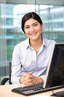 Businesswoman sitting at desk in office, beside flat screen computer, smiling, portrait, window in background