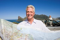 South Africa, Cape Town, mature man holding map by sea, smiling, portrait, woman by car in background