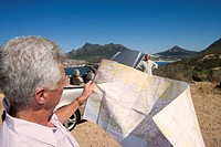 South Africa, Cape Town, mature man looking at map, woman by car in background