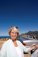 South Africa, Cape Town, mature woman standing outdoors by car and sea, smiling, portrait, close-up