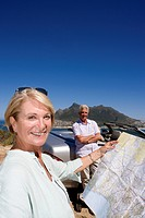 South Africa, Cape Town, senior woman holding map outdoors, senior man in background by car, smiling, portrait
