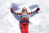 Girl 7-9 lying in snow making ´angel wings´, smiling, overhead view