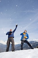 Two young men catching snow falling from sky, laughing, mountain range in background