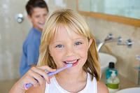 Boy and girl 6-8 brushing their teeth in bathroom, smiling, portrait, girl in foreground