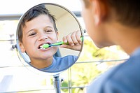 Boy 6-8 brushing teeth in bathroom, looking at reflection in mirror