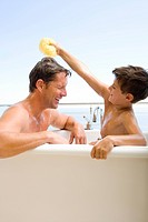 Father and son 6-8 in bath, boy holding sponge above man's head, side view