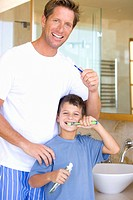Father and son 6-8 brushing their teeth in bathroom, smiling, portrait