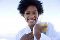 Young woman holding glass of juice outdoors, smiling, portrait, close-up
