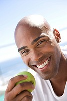 Young man holding green apple, smiling, portrait, close-up