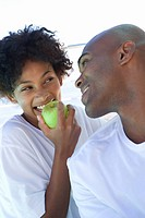 Young couple smiling outdoors, woman eating green apple
