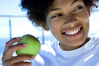 Young woman holding green apple outdoors, smiling, close-up