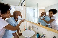 Young couple in bathroom, woman putting shaving foam on man's face, smiling