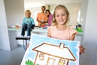 Girl6-8 holding painting of house, smiling, portrait, family in background