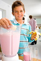 Boy 6-8 making fruit smoothie in kitchen, smiling, portrait
