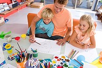 Father sitting with son and daughter6-8 art and crafts table, smiling, elevated view
