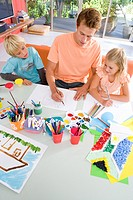 Father sitting with son and daughter6-8 art and crafts table, elevated view