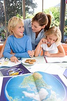 Mother by son and daughter 6-8 with homework, smiling, world atlas in foreground