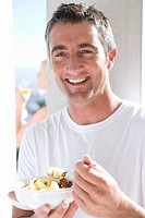 Man eating fruit salad outdoors, smiling, portrait, woman in background