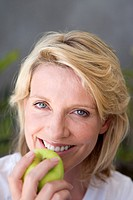Woman holding green apple, smiling, portrait, close-up