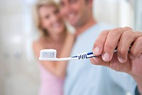 Woman embracing man holding up toothbrush, smiling, portrait focus on toothbrush