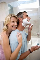 Woman embracing man in bathroom, man putting shaving foam on face, smiling, side view
