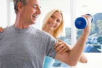 Mature woman smiling at mature man lifting weights, close-up