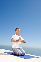 Mature man meditating on exercise mat outdoors, sea in background