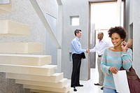 Woman holding house keys, smiling, portrait, male real estate agent shaking hands with man in background by stairs