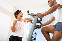Woman smiling at man on stationary bicycle, low angle view