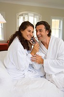 Couple wearing white bath robes on bed, both holding telephone receiver, smiling