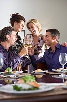 Four friends toasting drinks at table, smiling plate of salmon and salad in foreground