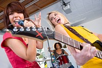 Three teenagers 15-17 in garage band, teenage girls singing and playing guitar in foreground