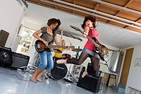 Three teenagers 15-17 playing electric guitars and drums in garage band