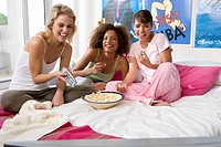 Three teenage girls 15-17 sitting on bed with popcorn, smiling, portrait