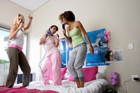 Three teenage girls 15-17 standing on bed, singing, low angle view