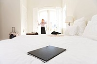 Laptop on bed, woman standing by window in background