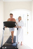 Mature woman standing by mature man on running machine indoors, smiling