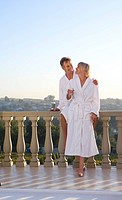 Mature couple wearing white bath robes, standing on balcony, smiling at each other