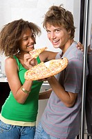 Teenage couple 16-18 standing by fridge with pizza, smiling, portrait of boy