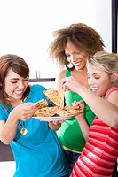 Three teenage girls 16-18 eating pizza, smiling