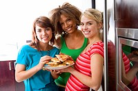 Three teenage girls 16-18 eating pizza, smiling, portrait