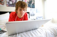 Teenage boy 16-18 lying on bed using laptop