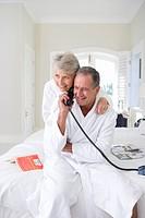 Senior couple using telephone on bed smiling