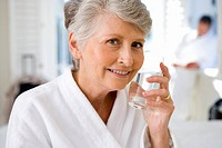 Senior woman holding glass of water to face, smiling, portrait, close-up