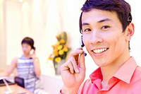 20's male receptionist using communications headset in reception with female receptionist in background