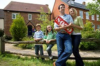 30's family with sold sign and house in background (thumbnail)