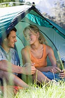 Young couple sitting in dome tent, holding camping mugs, smiling differential focus