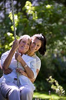 Senior woman swinging on garden rope swing, adult daughter embracing her, smiling, front view, portrait