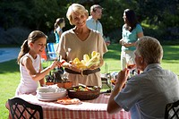 Three generation family having barbecue in summer garden, girl 8-10 standing beside grandmother at table, woman serving corn cobs, smiling