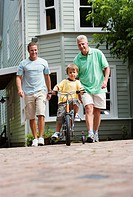 Boy 4-6 riding bicycle with stabilisers on pavement, father and grandfather looking on, smiling, front view, portrait surface level